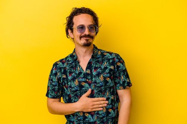 노란색 벽에 고립 된 여름 옷을 입고 젊은 백인 남자는 배를 만지고, 부드럽게 미소, 식사 및 만족 개념.