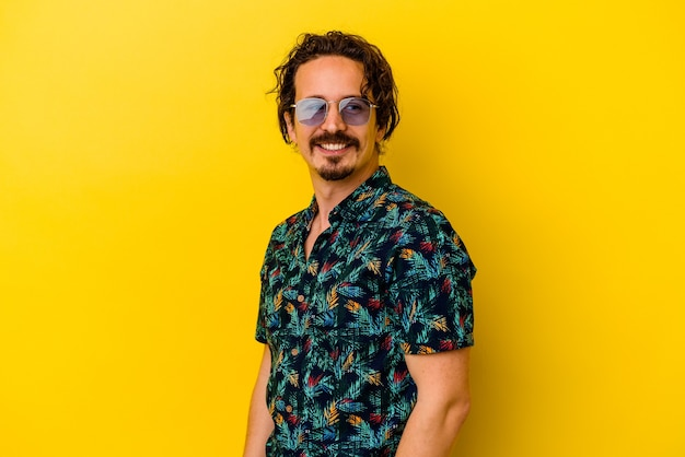 Young caucasian man wearing summer clothes isolated on yellow background looks aside smiling, cheerful and pleasant.