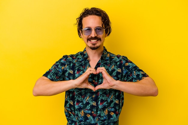 Young caucasian man wearing summer clothes isolated on yellow background smiling and showing a heart shape with hands.