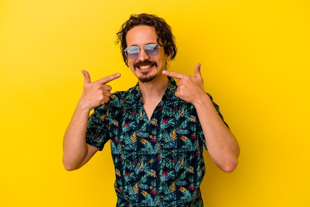Young caucasian man wearing summer clothes isolated on yellow wall smiles, pointing fingers at mouth