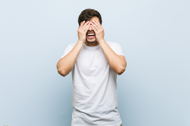Young caucasian man wearing a white tshirt covers eyes with hands, smiles broadly waiting for a surprise.