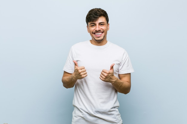 Young caucasian man wearing a white tshirt raising both thumbs up, smiling and confident.