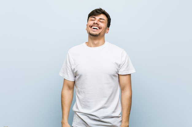 Young caucasian man wearing a white tshirt relaxed and happy laughing, neck stretched showing teeth.