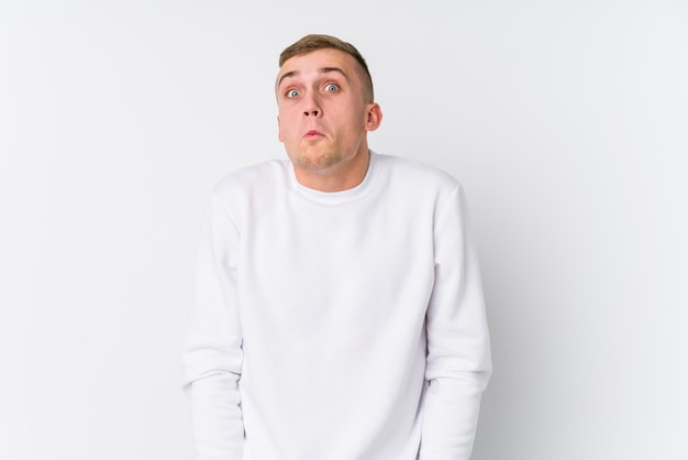Young caucasian man on white background shrugs shoulders and open eyes confused.