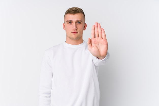 Young caucasian man on white standing with outstretched hand showing stop sign, preventing you.