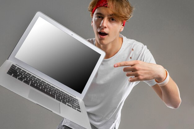 Young caucasian man on white t-shirt posing with laptop on grey wall