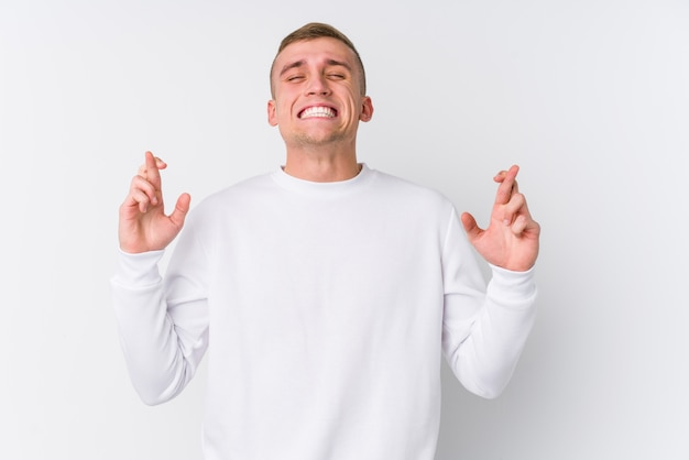 Young caucasian man on white wall crossing fingers for having luck