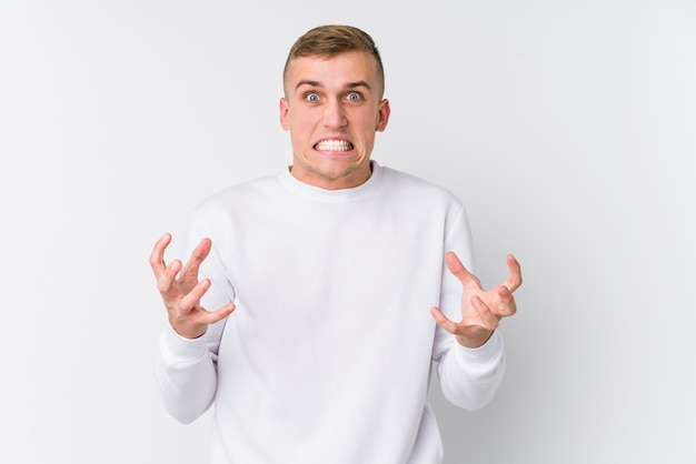 Young caucasian man on white wall upset screaming with tense hands.