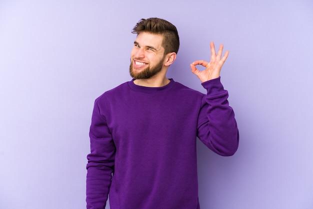 Молодой кавказский человек подмигивает и держит рукой жест.