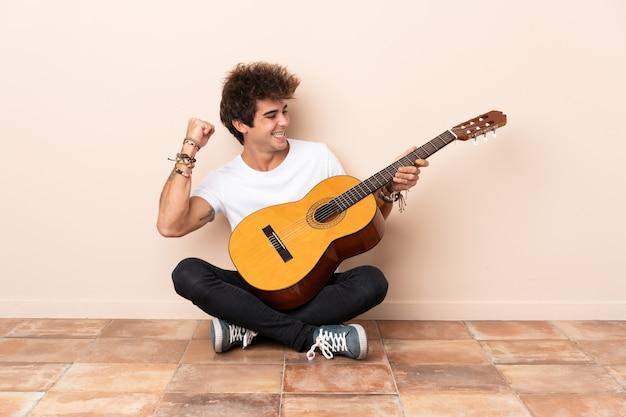 Молодой человек кавказской с гитарой, сидя на полу, празднует победу