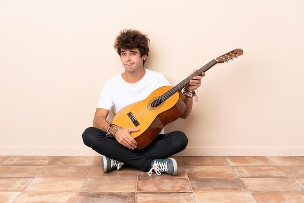 Молодой человек кавказской с гитарой, сидя на полу с грустным выражением