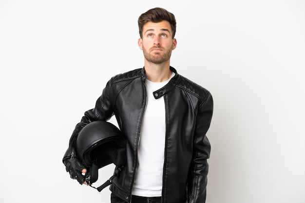 Молодой кавказский человек с мотоциклетным шлемом, изолированные на белом фоне и глядя вверх