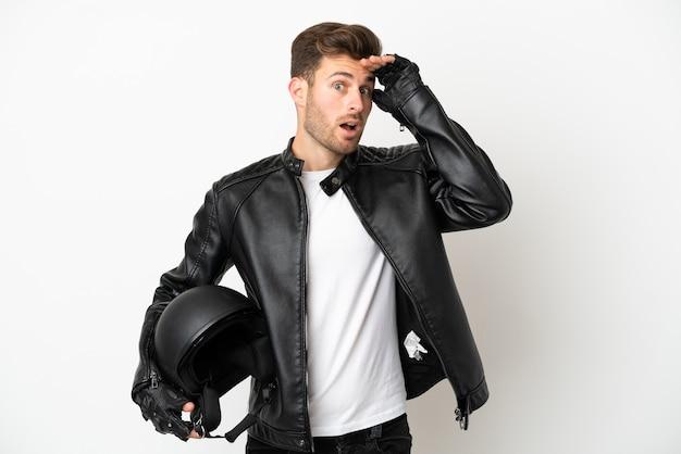 横を見ながら驚きのジェスチャーをしている白い背景で隔離のオートバイのヘルメットを持つ若い白人男性