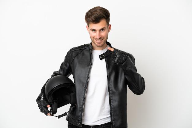 親指を立てるジェスチャーを与える白い背景で隔離のオートバイのヘルメットを持つ若い白人男性
