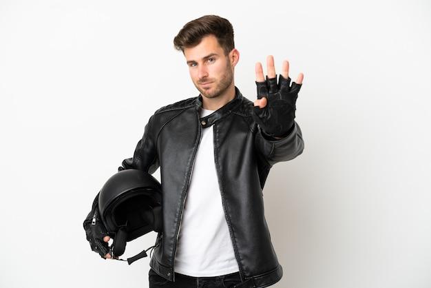 Молодой кавказский человек с мотоциклетным шлемом на белом фоне счастлив и считает четыре пальцами