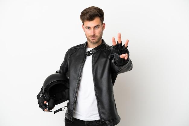 Молодой кавказский человек с мотоциклетным шлемом на белом фоне счастлив и считает три пальцами