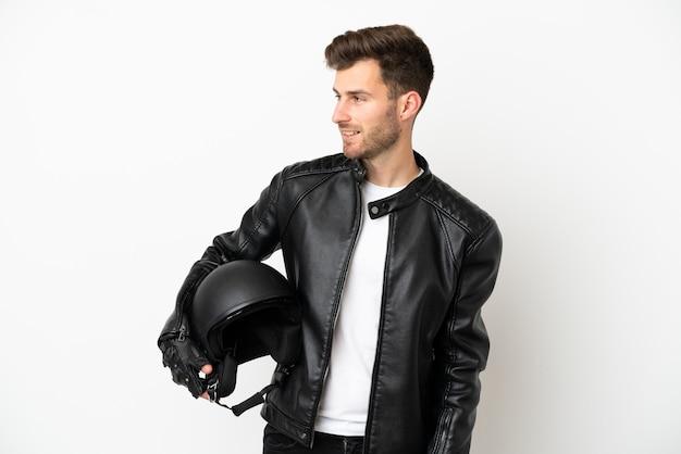 Молодой кавказский человек с мотоциклетным шлемом на белом фоне смотрит в сторону и улыбается