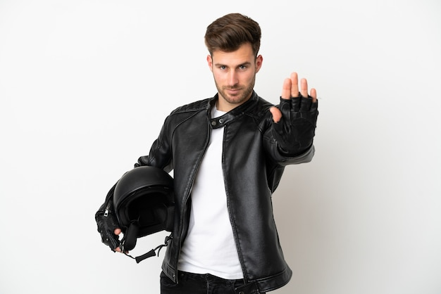 Молодой кавказский человек в мотоциклетном шлеме на белом фоне делает стоп-жест