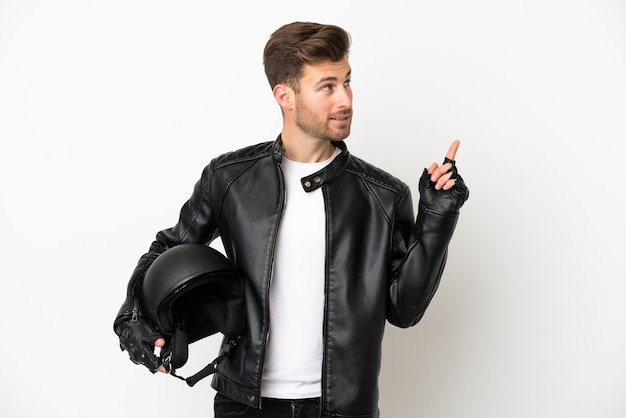 Молодой кавказский мужчина в мотоциклетном шлеме на белом фоне, указывая на отличную идею