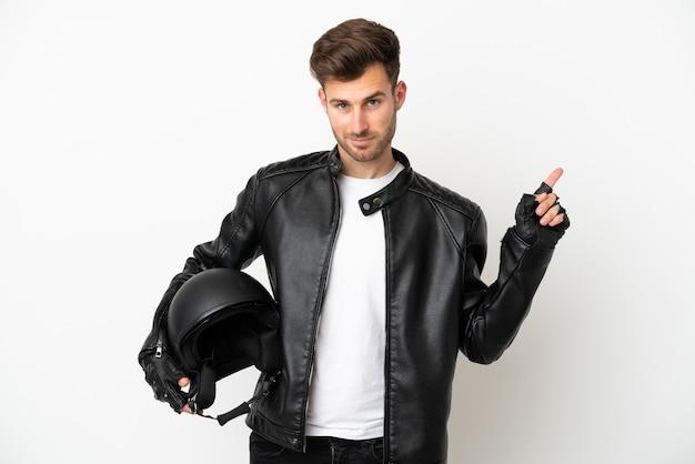 Молодой кавказский человек с мотоциклетным шлемом на белом фоне показывает и поднимает палец в знак лучших