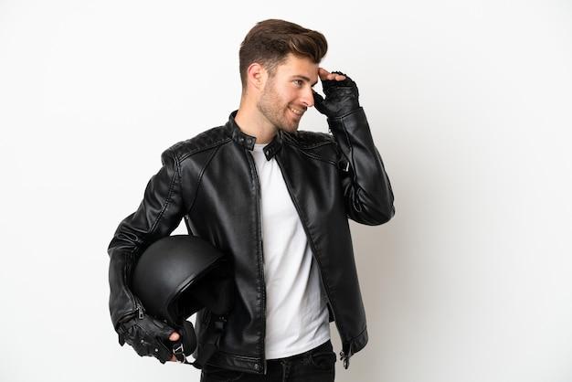 Молодой кавказский человек с мотоциклетным шлемом на белом фоне много улыбается