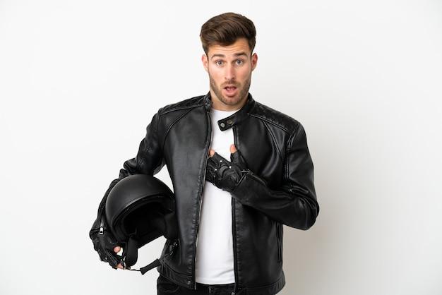 Молодой кавказский мужчина в мотоциклетном шлеме на белом фоне удивлен и шокирован, глядя вправо