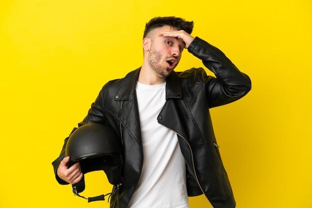 Молодой кавказец в мотоциклетном шлеме на желтом фоне делает неожиданный жест, глядя в сторону