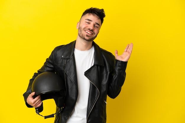 Молодой кавказский мужчина в мотоциклетном шлеме изолирован на желтом фоне, протягивая руки в сторону, приглашая приехать