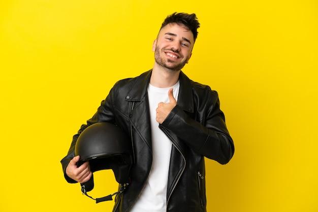 Молодой кавказский мужчина с мотоциклетным шлемом, изолированным на желтом фоне, показывает жест