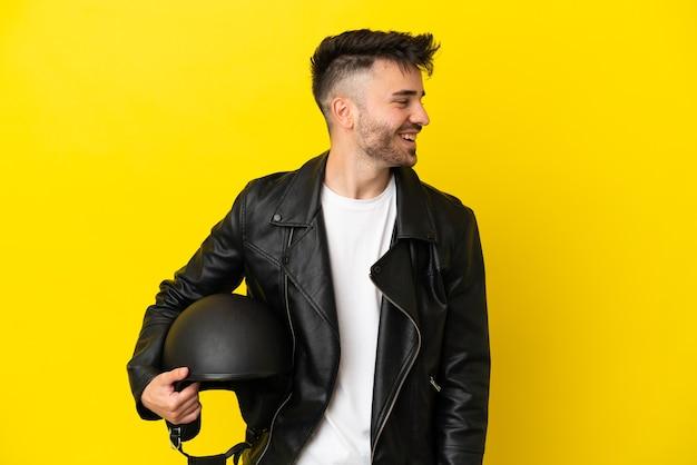 Молодой кавказский человек в мотоциклетном шлеме изолирован на желтом фоне, глядя в сторону