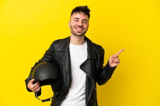 Молодой кавказский человек в мотоциклетном шлеме на желтом фоне, указывая в сторону, чтобы представить продукт