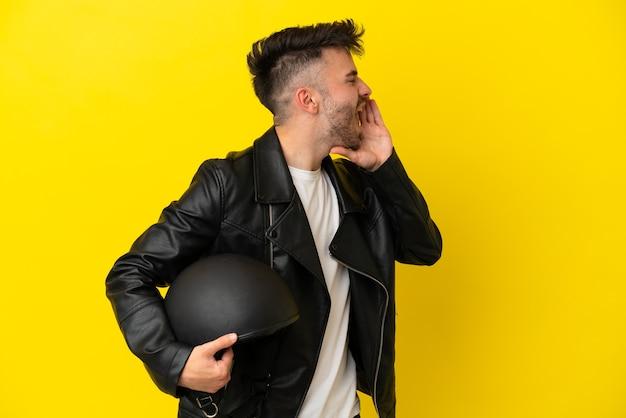 Молодой кавказец в мотоциклетном шлеме изолирован на желтом фоне и кричит с широко открытым ртом в сторону