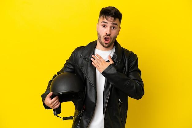 黄色の背景に分離されたオートバイのヘルメットを持つ若い白人男性は、右を見ながら驚いてショックを受けました