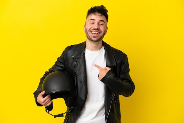 驚きの表情で黄色の背景に分離されたオートバイのヘルメットを持つ若い白人男性