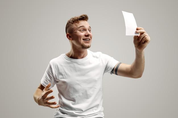 驚いた幸せな表情を持つ若い白人男性は、灰色のスタジオの背景に賭けを勝ち取りました。人間の顔の感情と賭けの概念
