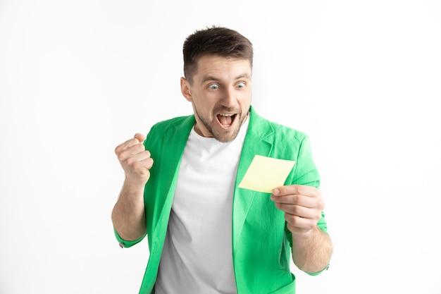 놀란 행복 한 표정으로 젊은 백인 남자는 회색 스튜디오 배경에 내기를 이겼다. 인간의 얼굴 감정과 도박 개념
