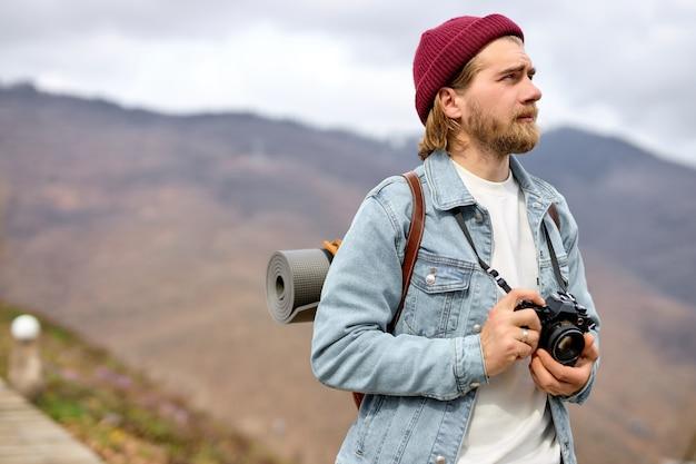 バックパックとカメラを持つ若い白人男性が遠くの山に向かって歩いています