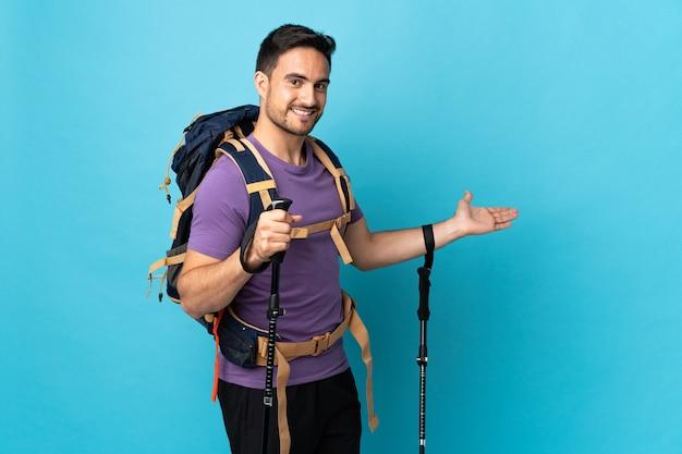 来るように誘うために手を横に伸ばして青い背景で隔離のバックパックとトレッキングポールを持つ若い白人男性
