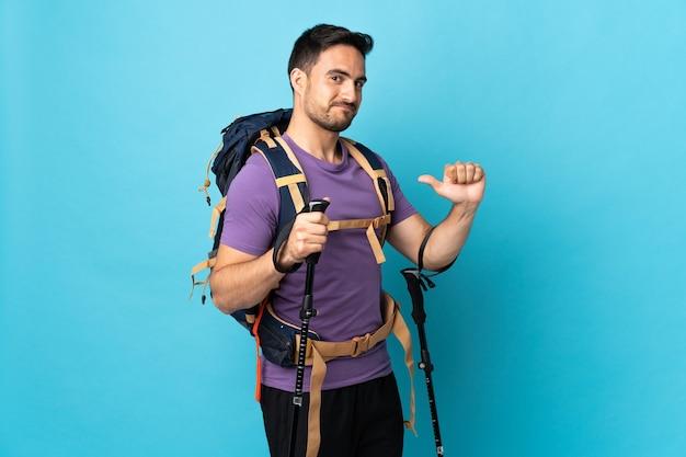 誇りと自己満足の青い背景に分離されたバックパックとトレッキングポールを持つ若い白人男性