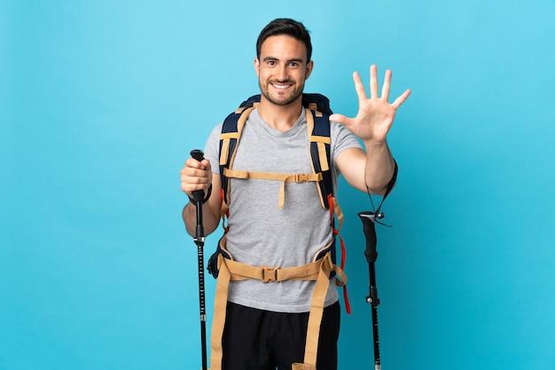 Молодой кавказский человек с рюкзаком и треккинговыми палками изолирован на синем, считая пять пальцами