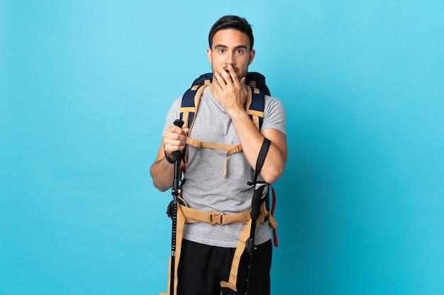 Молодой кавказский мужчина с рюкзаком и треккинговыми палками, изолированными на синей стене, удивлен и шокирован, глядя вправо