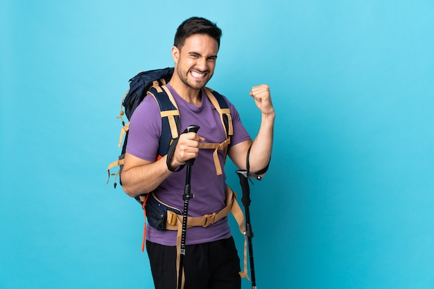 Young caucasian man with backpack and trekking poles isolated on blue background celebrating a victory