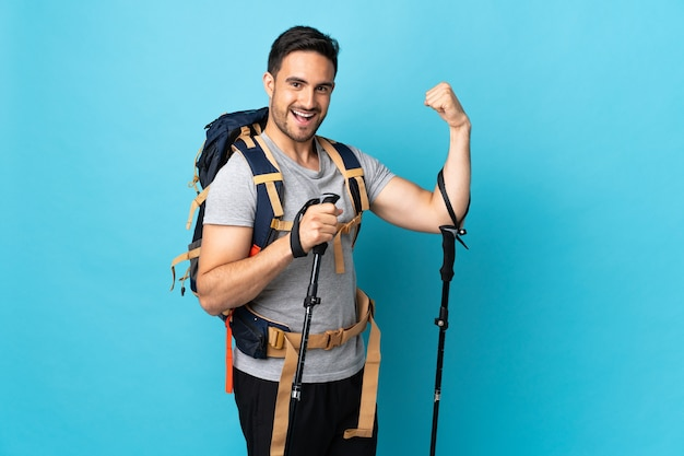 Young caucasian man with backpack and trekking poles isolated on blue background