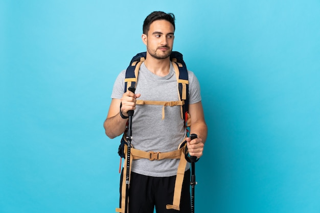 Young caucasian man with backpack and trekking poles isolated on blue having doubts while looking side