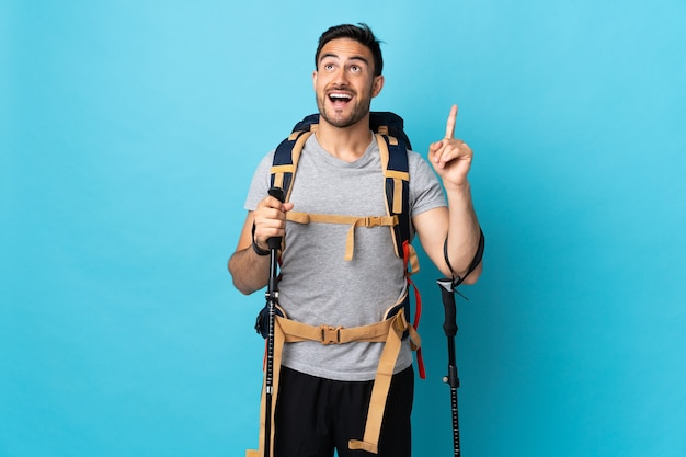 Young caucasian man with backpack and trekking poles isolated on blue wall pointing up and surprised