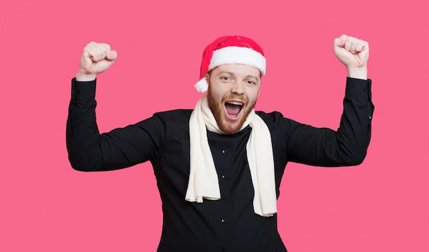 あごひげとスカーフを持つ若い白人男性は、赤い壁にサンタの帽子で叫んで勝利を身振りで示しています