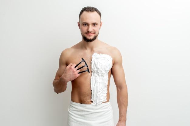 あごひげを生やした若い白人男性は、かみそりを持って白いシェービングフォームで胸を剃ります。胴体を剃る男