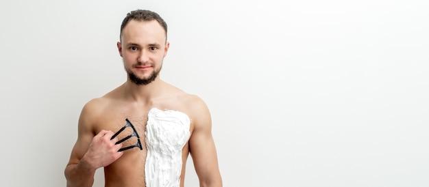 수염을 가진 젊은 백인 남자는 면도기를 보유하고 흰색 면도 거품으로 가슴을 면도합니다. 그의 몸통을 면도하는 남자