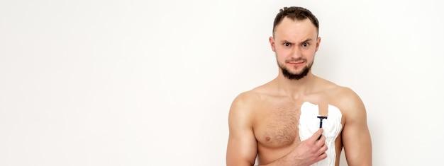 ひげを持つ若い白人男はかみそりを保持している白い表面に白いシェービングフォームで彼の胸を剃る。彼の胴体を剃る男