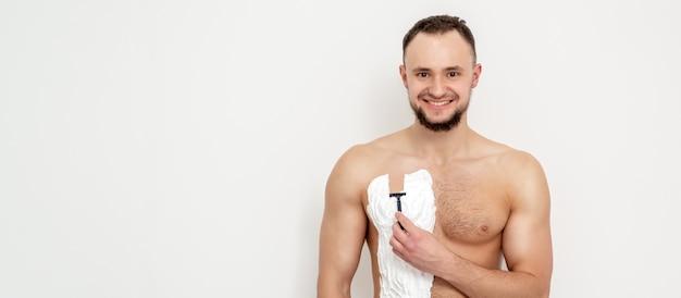 수염을 가진 젊은 백인 남자는 면도기를 보유하고 흰 벽에 흰 면도 거품으로 가슴을 면도합니다.